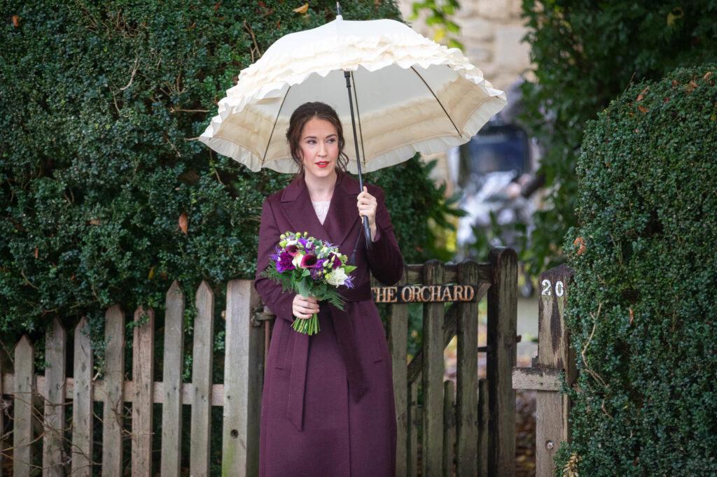 bride carries bouquet white umbrella st nicholas church old marston oxford ceremony oxfordshire wedding photography