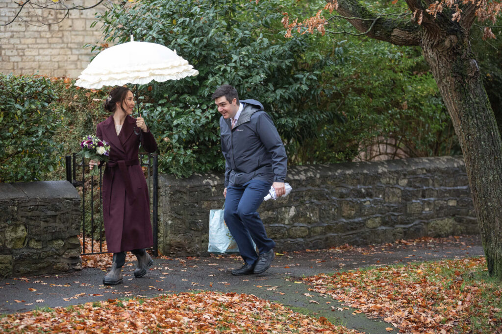 bride carries umbrella groom runs behind st nicholas church ceremony old marston oxford wedding photograher