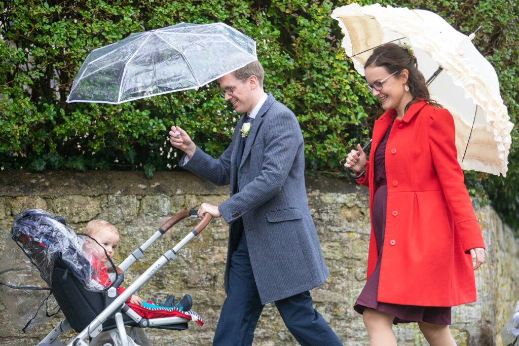 guest pushes baby stroller st nicholas church old marston village micro wedding oxfordshire wedding photographer