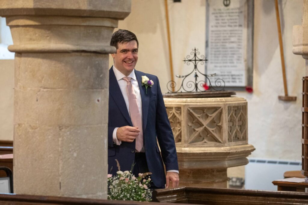 smiling groom enters st nicholas church micro wedding old marston village oxford wedding photographer