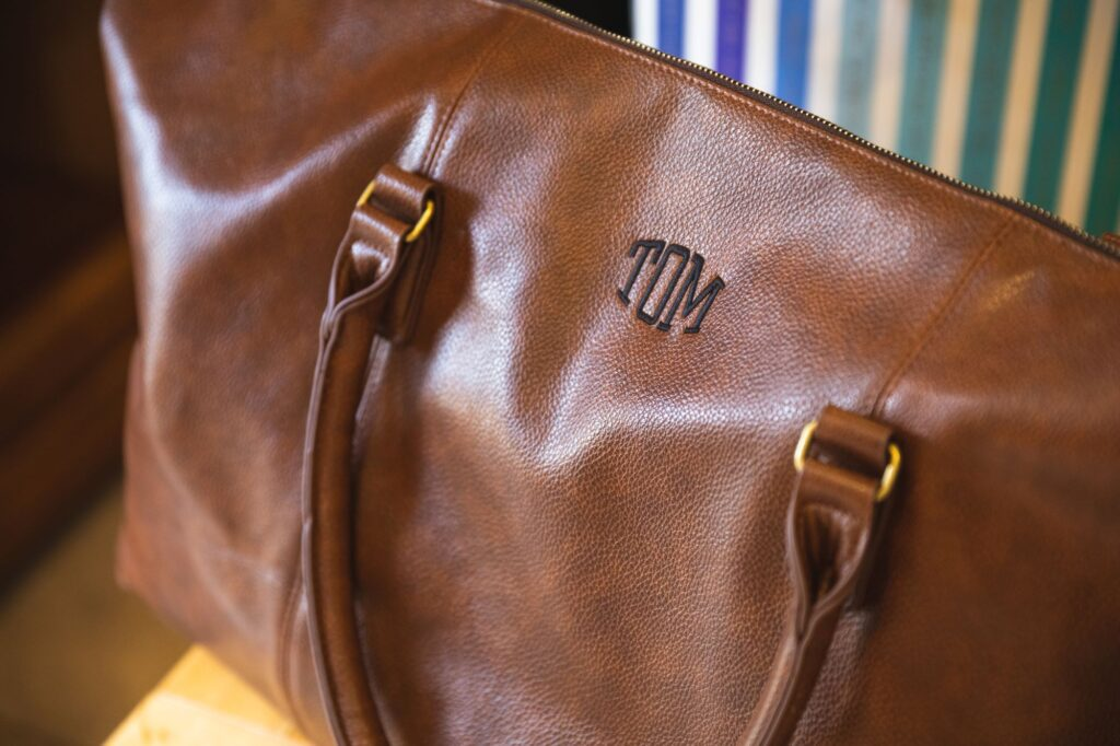 grooms name tag leather bag grooms prep caswell house venue oxfordshire wedding photographer