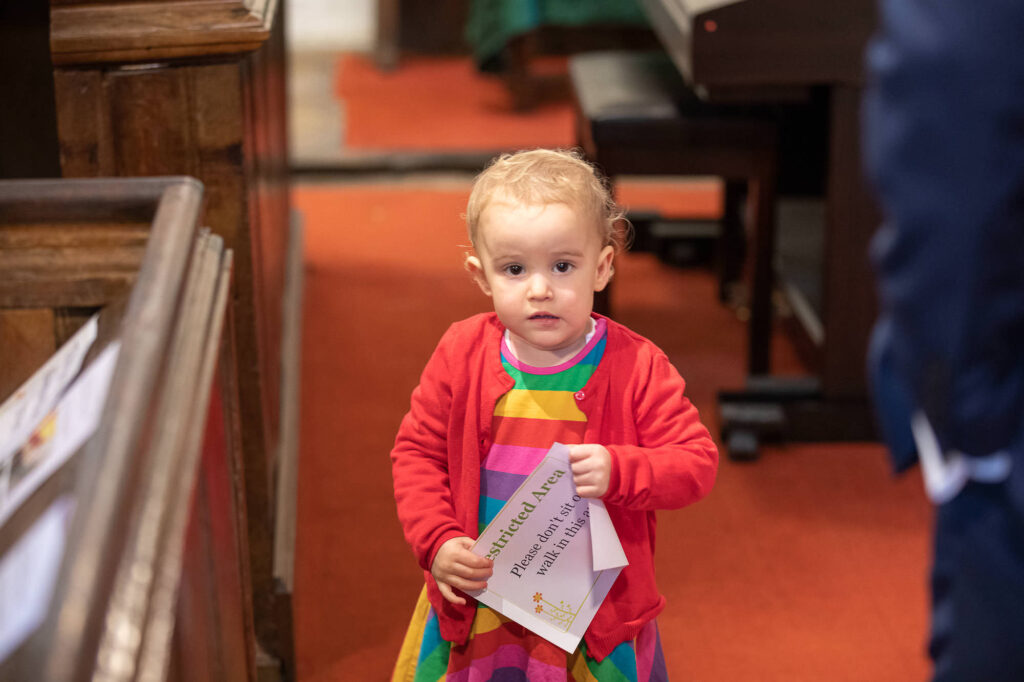 toddler holds notice st nicholas church ceremony old marston oxfordshire wedding photographers