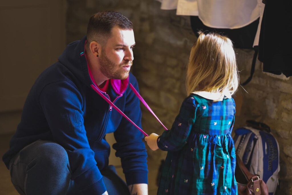groomsman with young girl groom prep caswell house venue oxfordshire wedding photographers