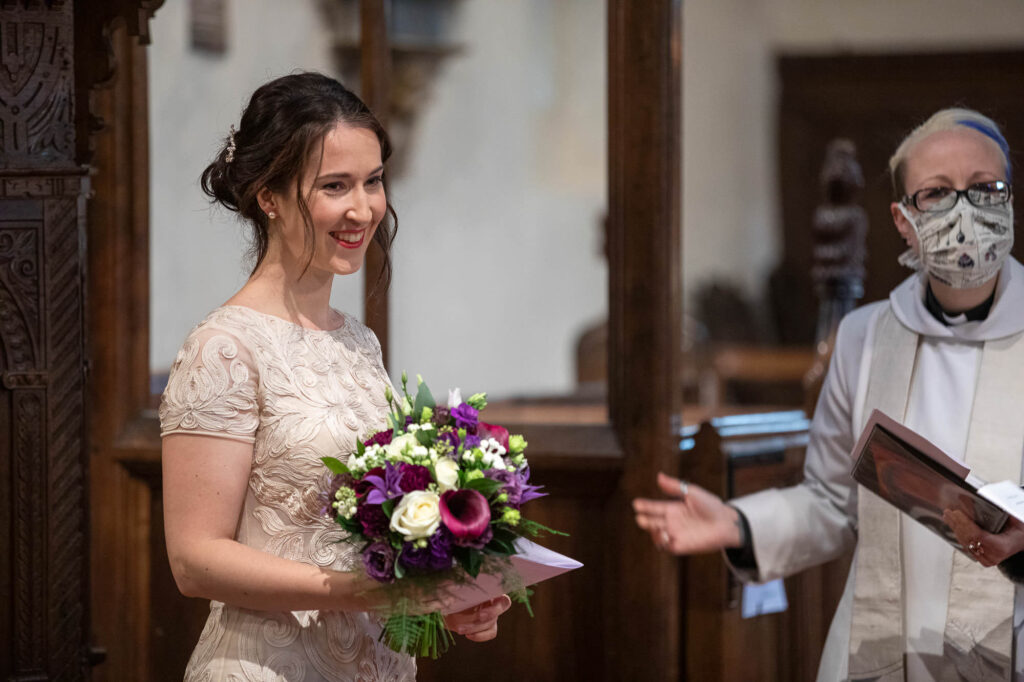 smiling bride covid masked vicar st nicholas church micro wedding ceremony old marston oxfordshire wedding photographers
