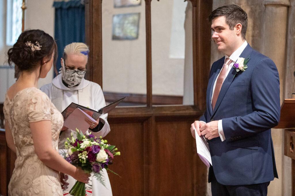 groom looks towards bride micro wedding ceremony st nicholas church old marston oxford wedding photographers