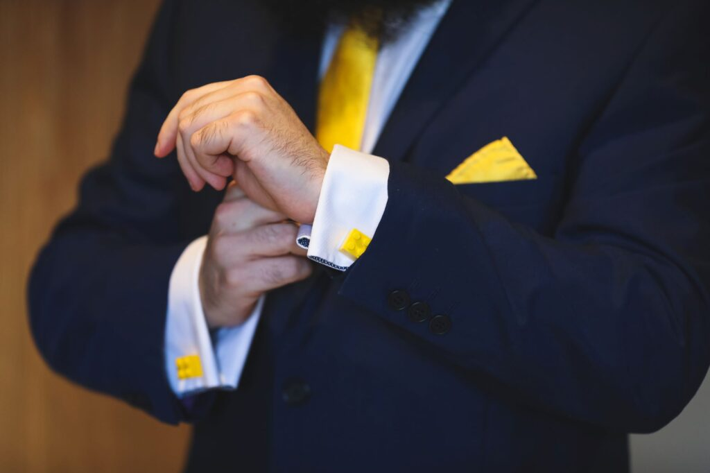 groom shows yellow cufflinks groom prep caswell house venue oxford wedding photographers