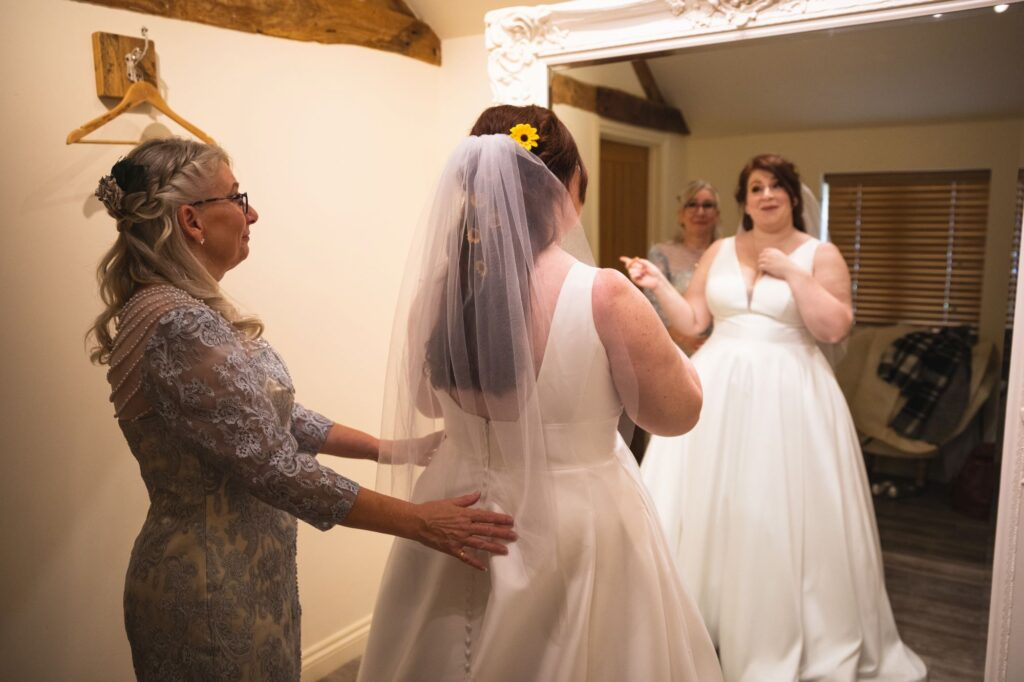 bride checks gown in mirror caswell house bridal prep oxfordshire wedding photographer
