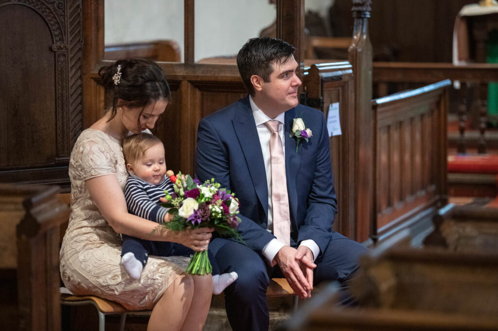 brides baby bride groom hear vicar covid marriage ceremony st nicholas church old marston oxfordshire wedding photography
