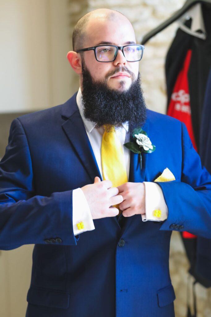 groom checks button hole corsage groom prep caswell house venue oxfordshire wedding photographry