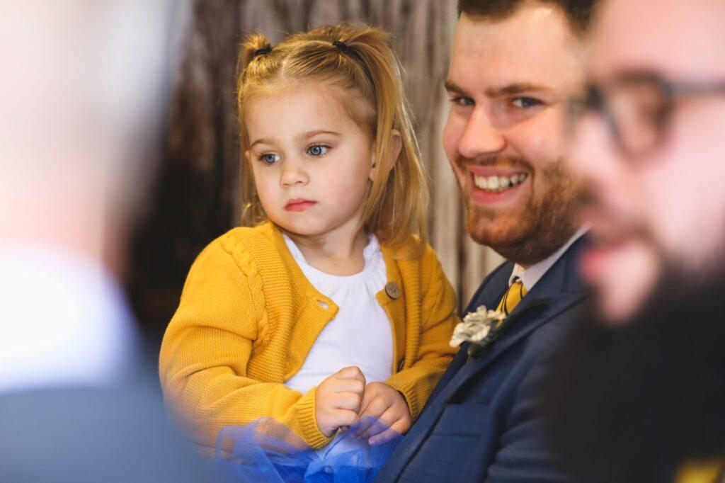 groomsman holds flowergirl caswell house venue oxford wedding photographer