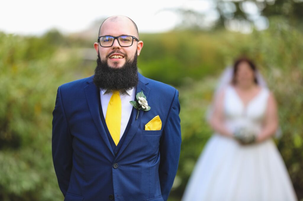 grooms awaits bride for first look caswell house venue oxfordshire wedding photographer