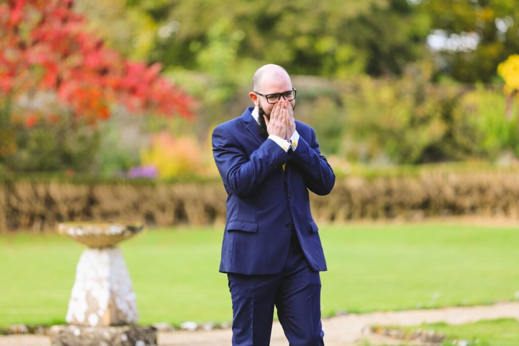 surprised grooms first look at bride caswell house gardens oxfordshire wedding photography