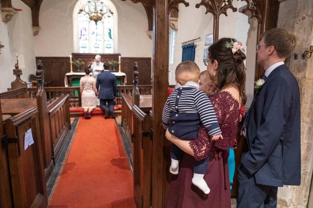 kneeling bride groom covid marriage ceremony st nicholas church oxford wedding photography