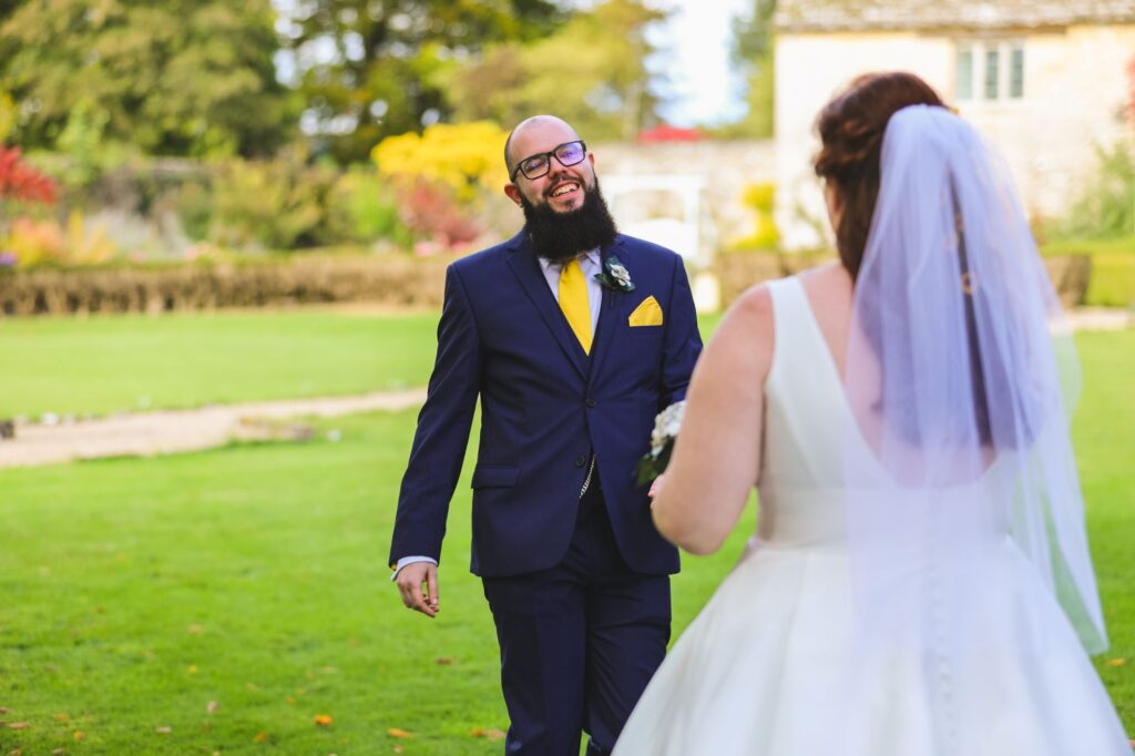 smiling groom approaches bride caswell house gardens oxford wedding photographer