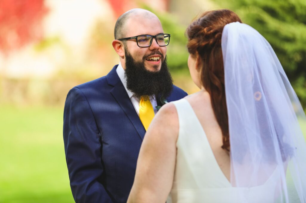 smiling groom holds brides hands caswell house gardens oxford wedding photographers
