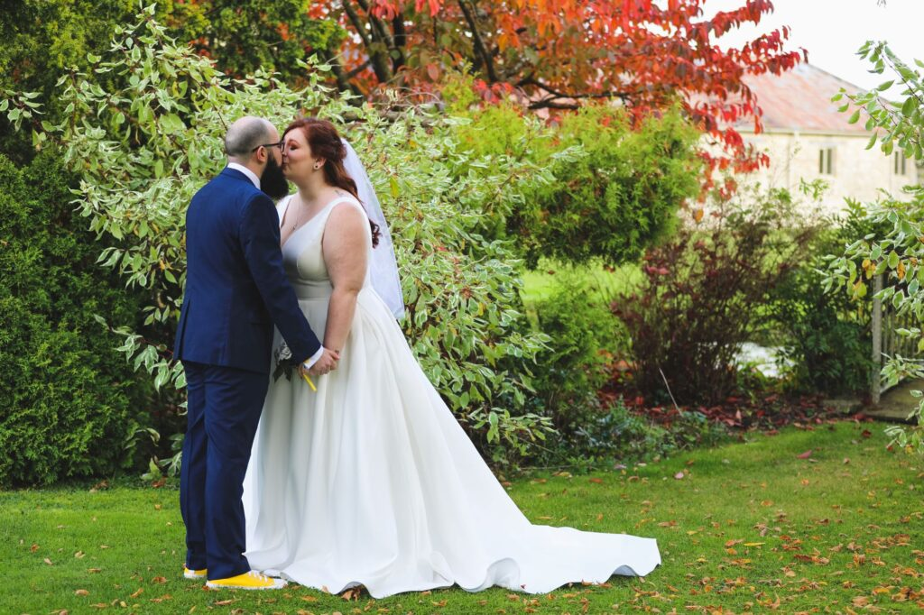groom kisses bride caswell house gardens oxford wedding photography