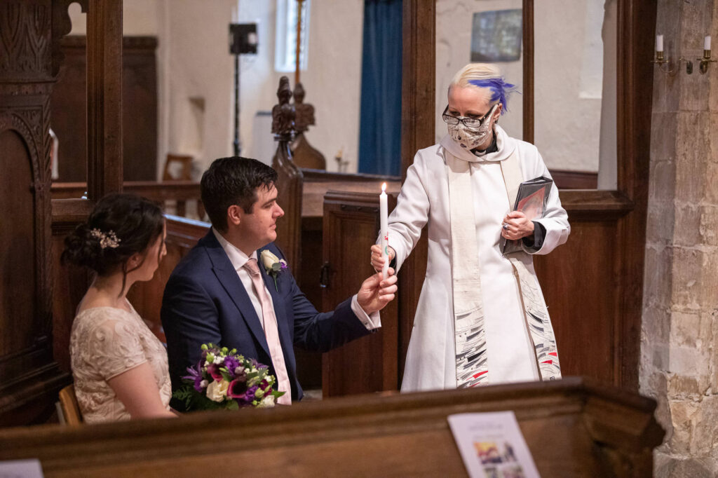 vicar hands groom candle covid marriage ceremony st nicholas church oxfordshire wedding photographers
