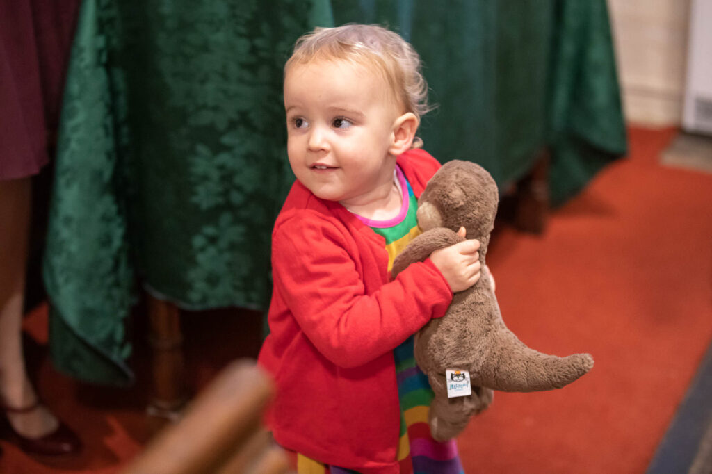 toddler holds cuddly toy st nicholas church marriage ceremony oxfordshire wedding photographer