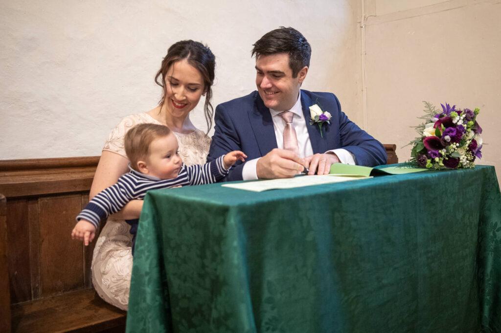 bride groom sign marriage register st nicholas church oxfordshire wedding photographers