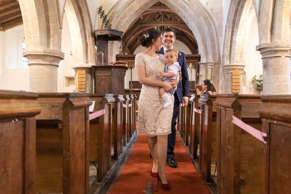 just married bride holds baby groom smiles st nicholas church oxford wedding photographer