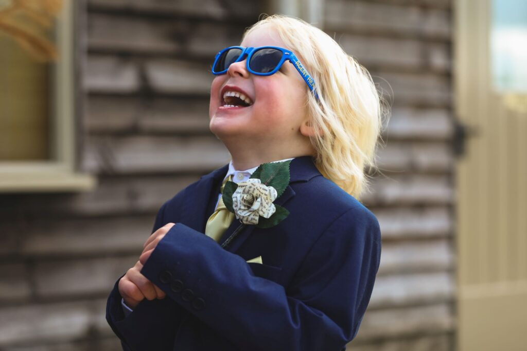 laughing pageboy in sunglasses caswell house venue oxford wedding photographer