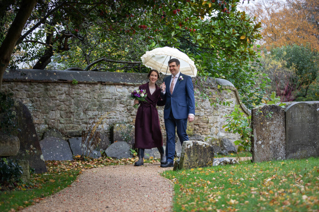 bride groom white umbrella st nicholas churchyard marston oxfordshire wedding photography