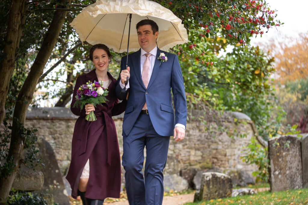 smiling bride bouquet groom holds white umbrella st nicholas churchyard marston oxford wedding photography