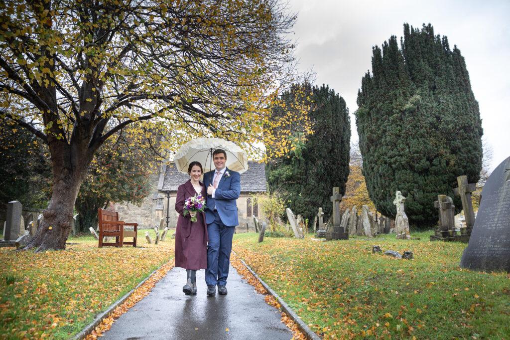 smiling bride groom holds umbrella leave st nicholas churchyard oxfordshire wedding photographer