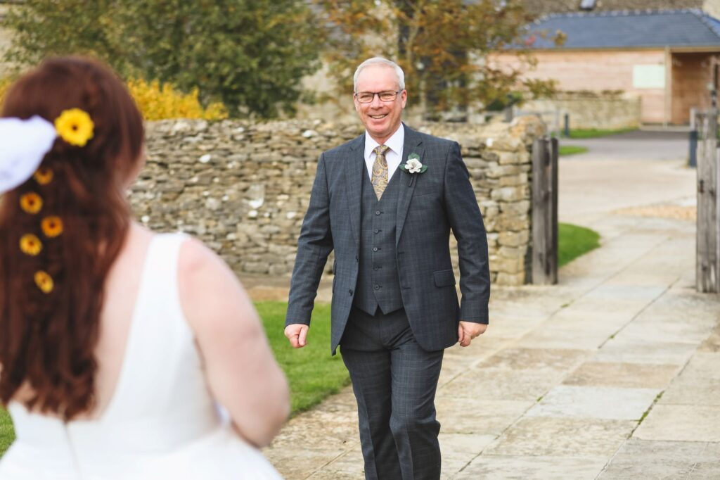 grinning father of bride sees daughter caswell house venue oxfordshire wedding photography