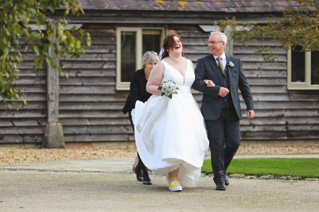 bride father of bride walk towards outdoor ceremony caswell house venue oxford wedding photographers