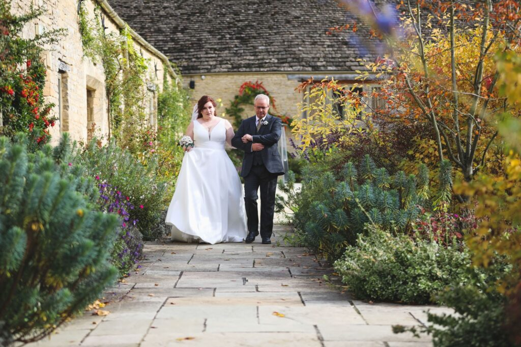 bride holds fathers arm walking through caswell house gardens oxfordshire wedding photographer