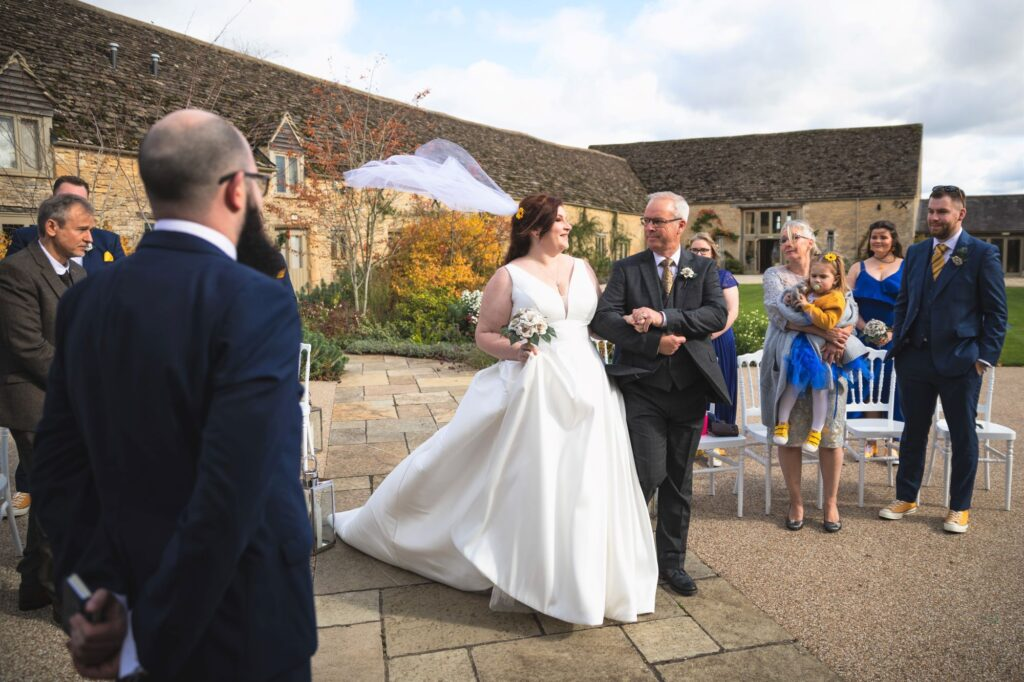 brides flowing veil outdoor ceremony caswell house venue oxfordshire wedding photographers