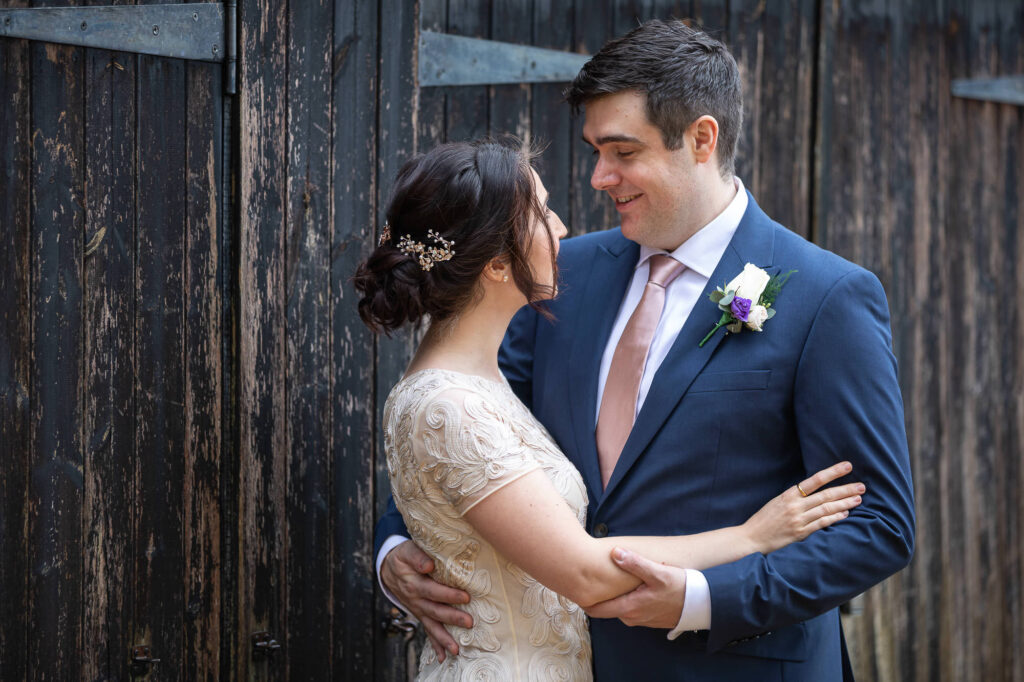 groom holds bride close orchard garden old marston village oxfordshire wedding photographer