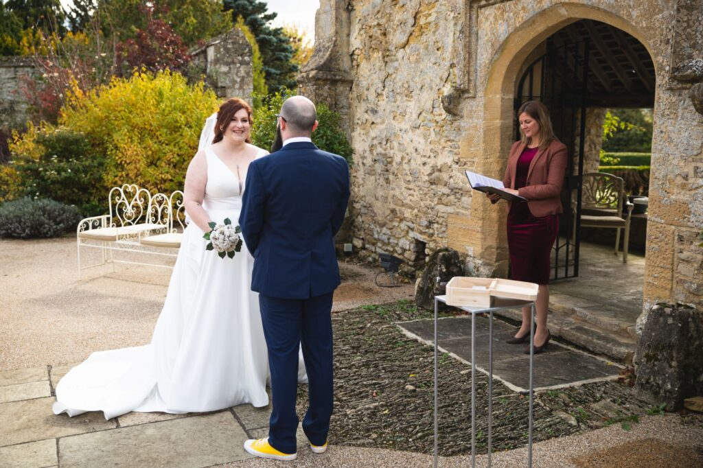 smiling bride groom celebrant outdoor ceremony caswell house venue oxfordshire wedding photography