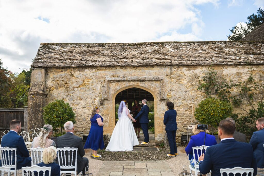 bride groom hold hands outdoor ceremony caswell house venue oxford wedding photographers