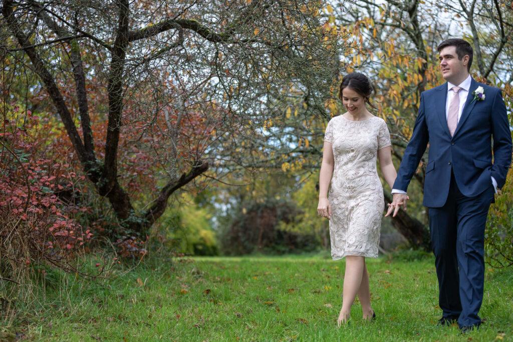 bride holds grooms hand orchard garden stroll old marston village oxfordshire wedding photography