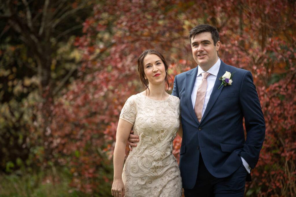 groom holds brides waist orchard garden walk old marston village oxford wedding photographer