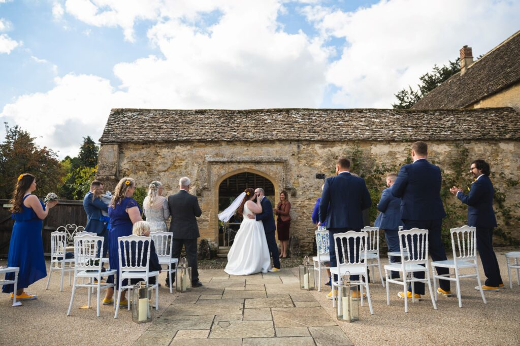 groom kisses bride outdoor ceremony caswell house venue oxford wedding photography