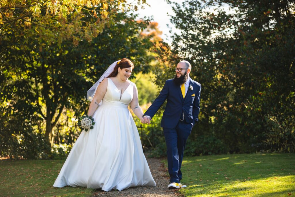 smiling bride groom hold hands caswell house grounds oxford wedding photographers