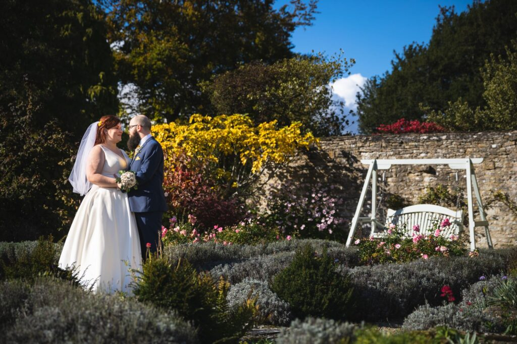 bride groom embrace caswell house cottage garden oxford wedding photography
