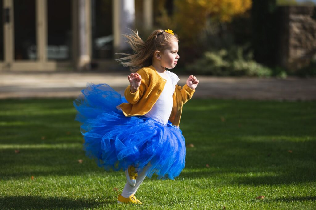 young girl blue party dress running caswell house gardens oxfordshire wedding photographer