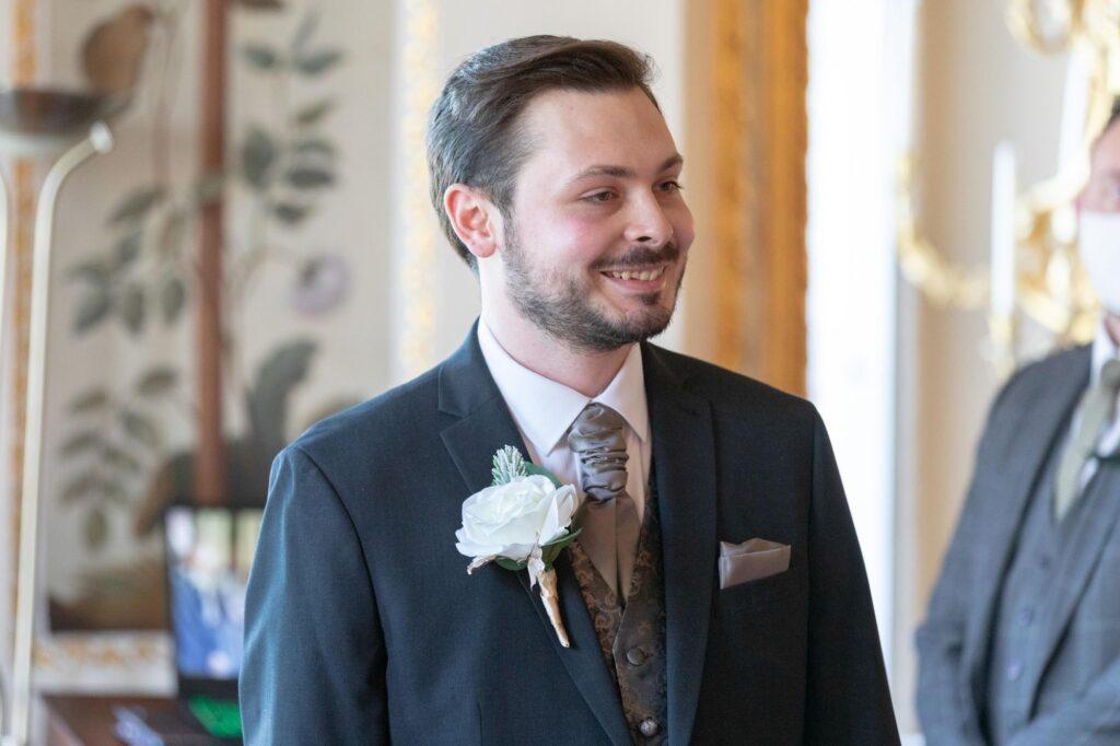 smiling groom sees bride enter danson house registry office ceremony bexleyheath oxfordshire wedding photography