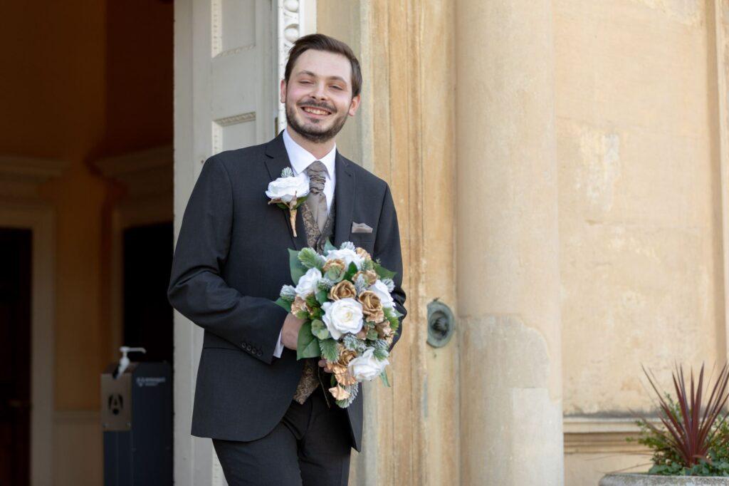 smiling groom carries brides bouquet danson house bexleyheath oxfordshire wedding photography