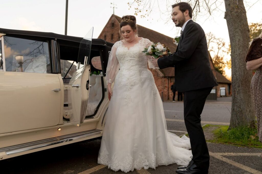 groom assists bride into bridal car danson house and park bexleyheath oxfordshire wedding photographers