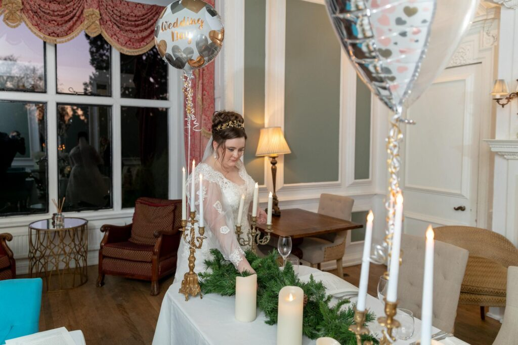 bride adjusts wedding breakfast table arrangement the manor at bickley oxfordshire wedding photographers