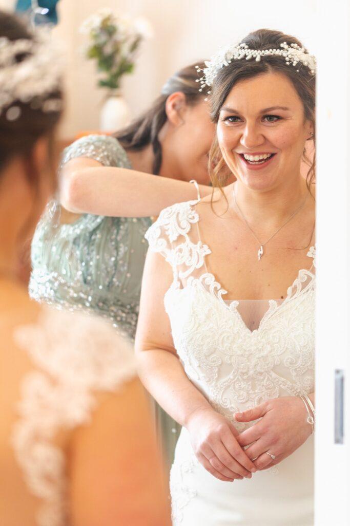 smiling brides mirror reflection bridal prep sowerby bridge marriage oxfordshire wedding photographers