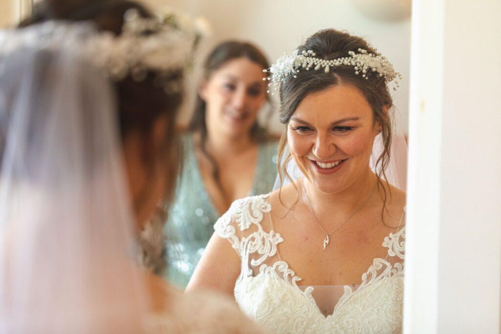 smiling bride mirror reflection bridal preparation sowerby bridge marriage oxford wedding photographers