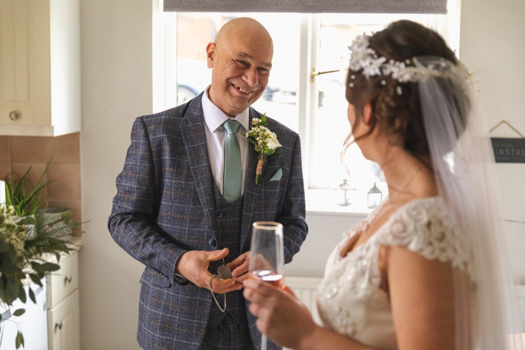 bride sips champagne father of bride smiles st johns church ceremony rishworth oxford wedding photographers