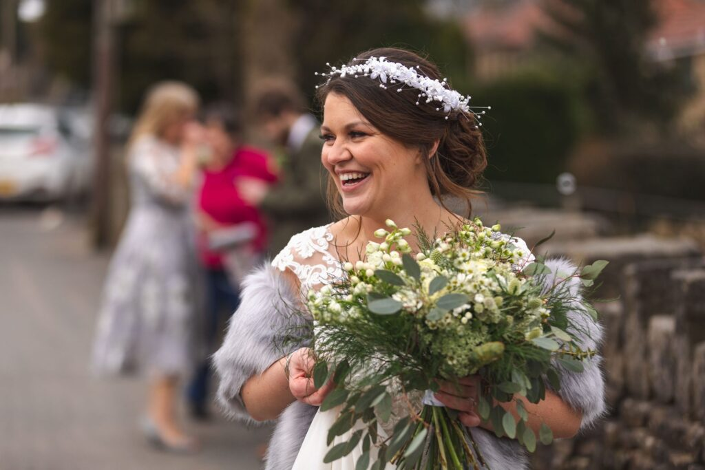 laughing bride holds bouquet st johns church ceremony rishworth oxford wedding photography