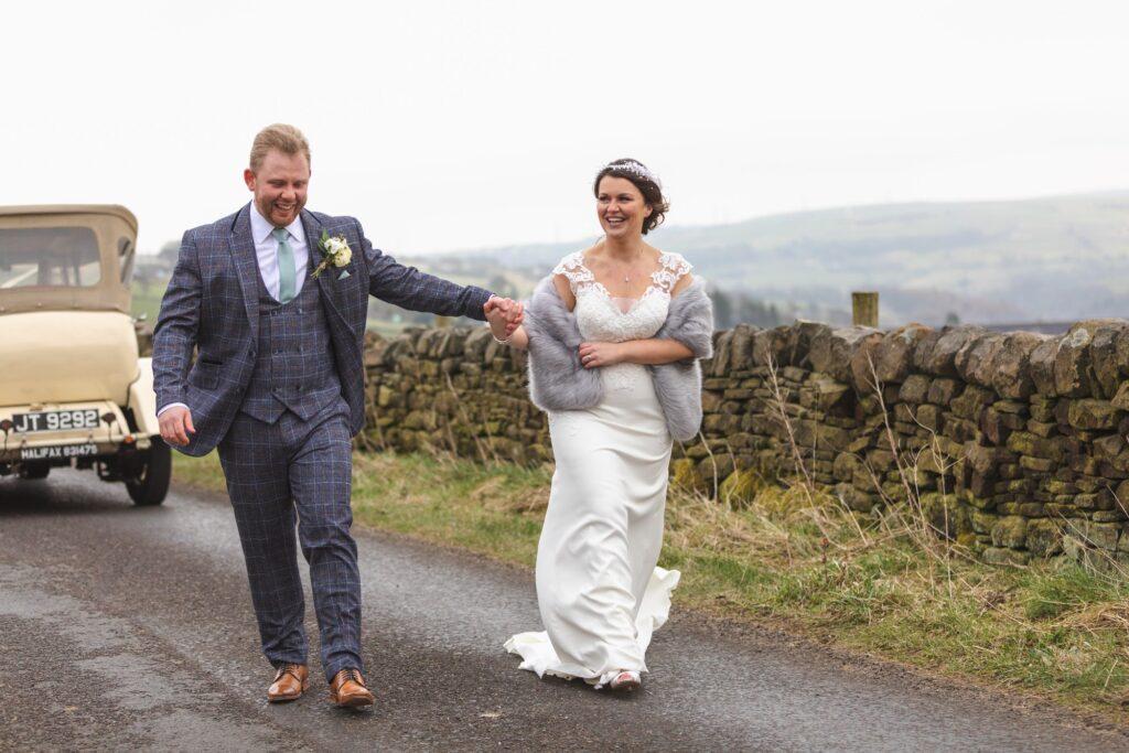 laughing bride groom hold hands countryside walk rishworth sowerby bridge west yorkshire oxford wedding photographers